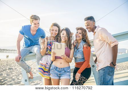 Friends With Tablet On The Beach