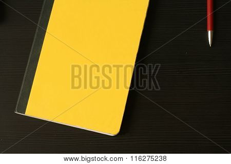 Top View On The Yellow Scratchpad (notebook) With Red Pencil