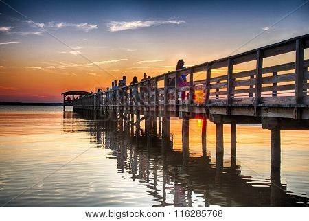 Fort Fisher, NC - August 14 2015 Fort Fisher Air Force Recreation Center Kure Beach North Carolina USA: Tourists watch the sunset from the pier jutting out over the Cape Fear River.