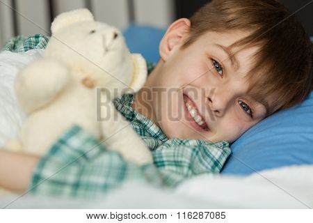 Happy Boy With His Teddy Bear Lying On His Bed