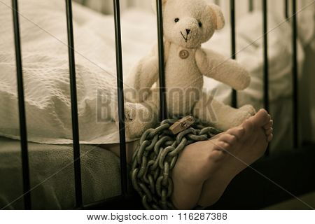 Tied Feet Of A Sleeping Boy With Teddy Bear On Top
