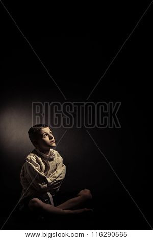 Thoughtful Lonely Boy Sitting In An Isolated Room