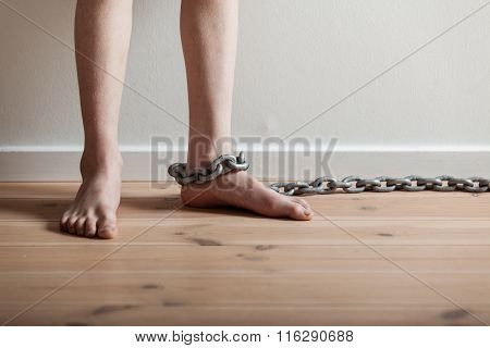 Conceptual Feet Of A Boy With Chain Inside A Room