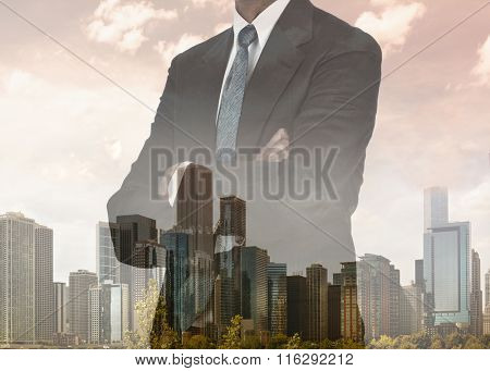 Double exposure of a businessman with his arms folded with city background.