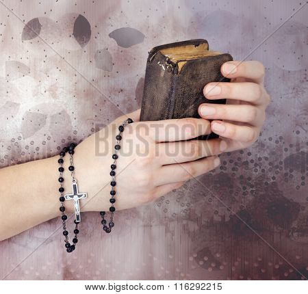 Young Woman's Hands With A Rosary And A Bible