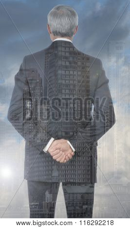Double exposure of a businessman with his hands clasped behind his back with city background.