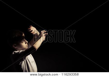Boy Looking Up While Covering Light Against Black