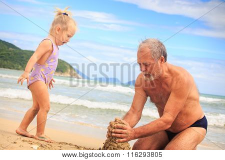 Grandpa Little Blond Girl Play With Wet Sand On Beach By Surf
