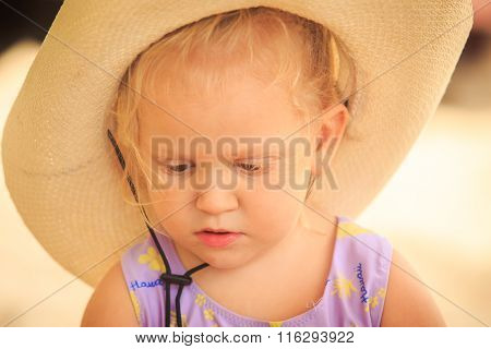 Closeup Portrait Of Little Blond Girl In Hat Against Sand