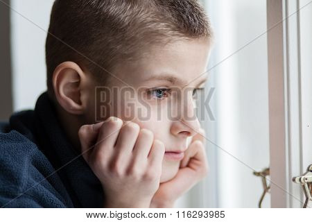 Pensive Boy Leans His Face On Hands At The Window
