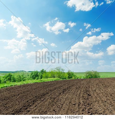 black agriculture field and white clouds in blue sky on spring