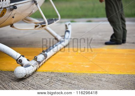 landing skid of helicopter with pilot background