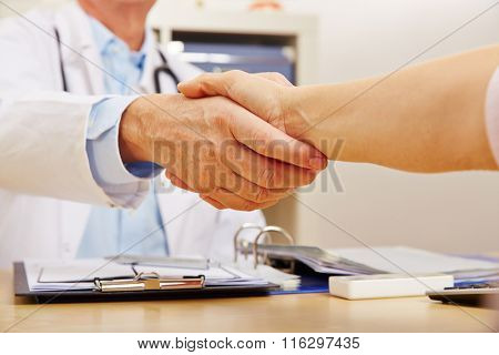 Handshake with doctor and patient at the desk in the doctor's office