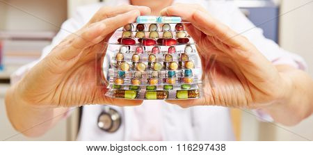 Hands of doctor holding stack of colorful pills and medicine