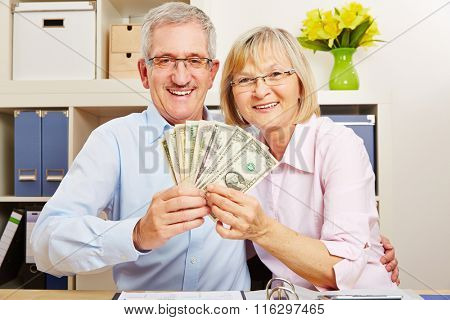 Happy senior couple with money fan made of dollar bills