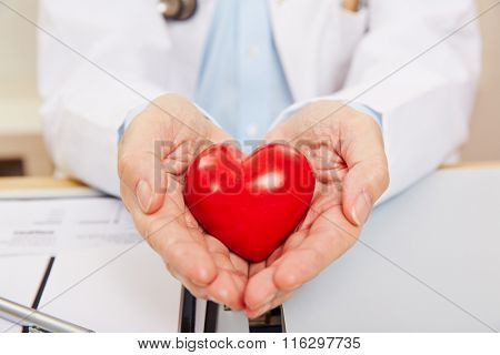 Hand of a doctor holding a red heart as symbol for cardiology