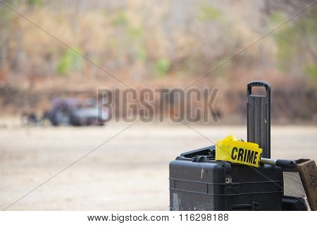 crime scene tool box with wrecked car background in car bomb crime scene