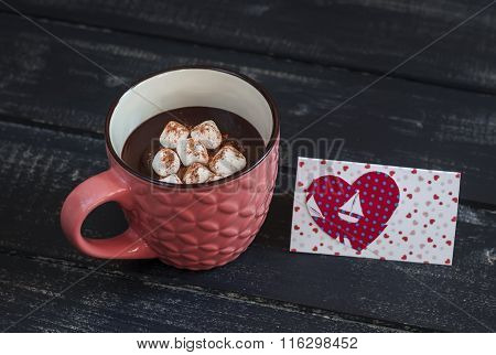 Cup Of Hot Chocolate With Marshmallows And  Valentine's Day Poscard On Dark Wooden Background