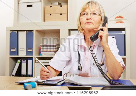 Elderly female doctor sitting at emergency service telephone in the office