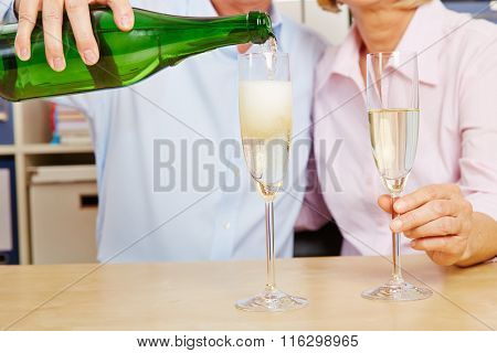 Old couple pouring champagne in glass for New Year's Eve