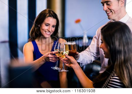 Friends toasting together in a bar