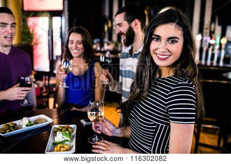 Portrait of woman having an aperitif with friends in a bar