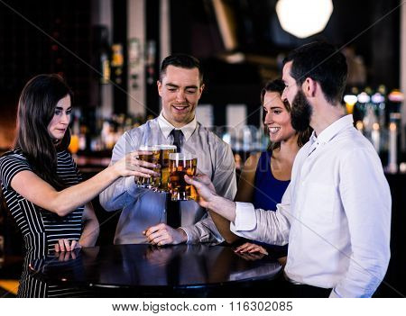 Friends toasting with a beer in a bar
