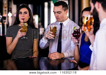 Friends drinking cocktails and beers in a bar