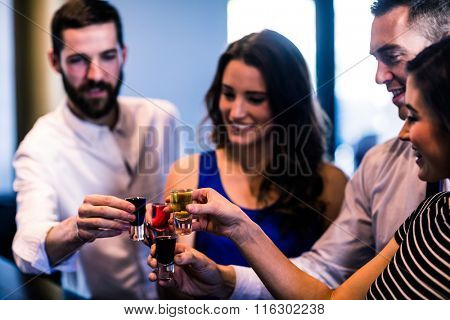 Friends toasting with alcohol shots in a bar