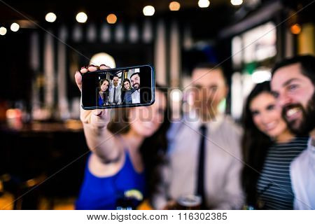 Group of friends taking a selfie in a bar