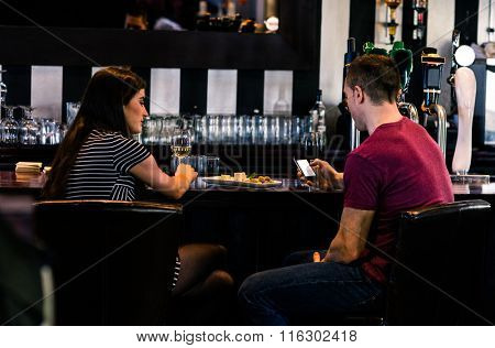 Couple having a glass of wine while man is texting in a bar