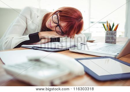 Hipster businesswoman falling in sleep at her desk in office
