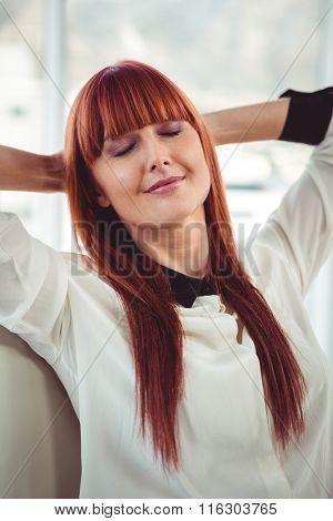 Hipster businesswoman with outstretched arms in office