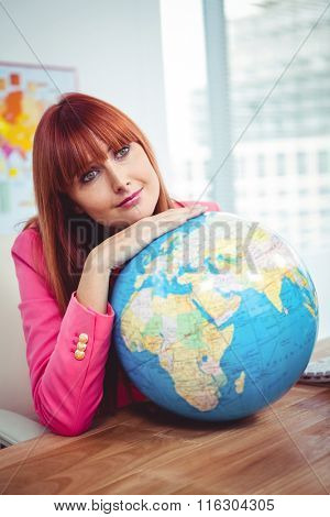 Hipster businesswoman lean on a globe in office