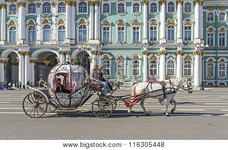 People In Carriage At Palace Square Near Winter Palace Of St. Petersburg