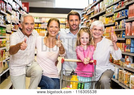 Happy extended family showing thumbs up at the supermarket