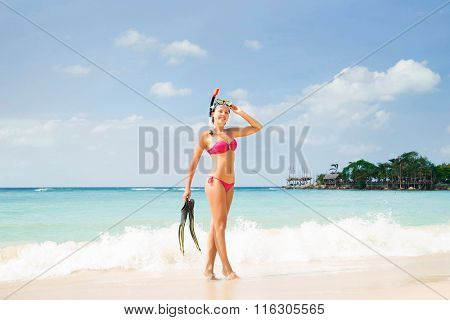 Cheerful, beautiful girl with slim body posing on the seacoast with scuba mask and flippers.