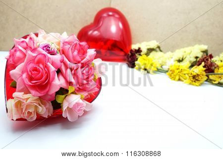 Fabric colorful roses in red heart shaped box on white floor, blurred wooden background
