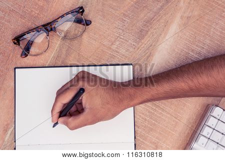 Cropped image of businessman writing on notebook by eyeglasses at desk in office