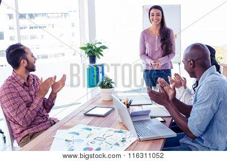 Business people applauding for female coworker in creative office