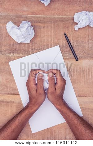 Cropped image of businessman making paper balls at desk in office