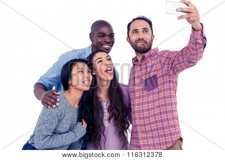 Happy multi-ethnic friends making face while taking selfie against white background