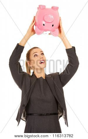 Business woman shaking a piggybank.