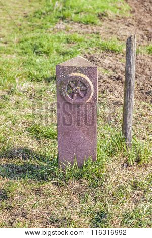 historic boundary stone in the green field