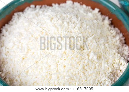 Ceramic bowl full of fresh grated cheese.