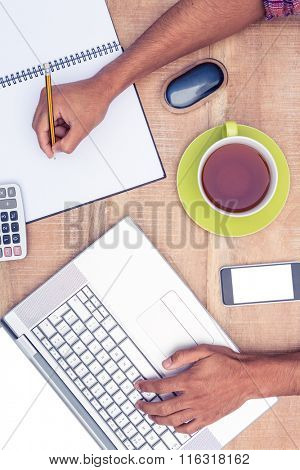 Businessman working on laptop while writing on book at desk in office