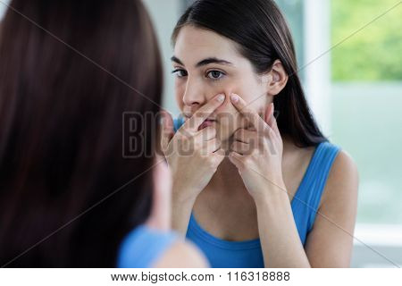 Unhappy woman with skin irritation cleaning her face at home