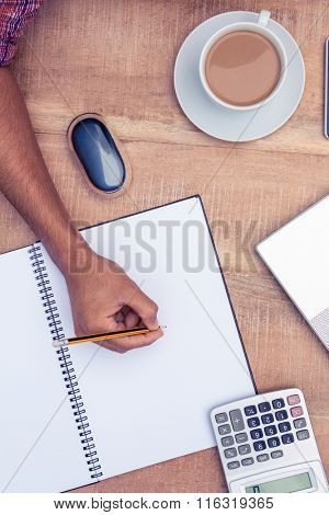 Cropped image of businessman writing on notebook at desk in office