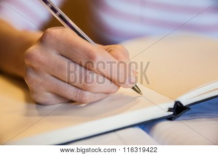 Female student writing notes at the university
