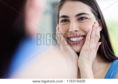 Smiling brunette in bathroom looking at the mirror